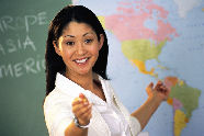 Photo of a teacher in front of a blackboard and a world map.